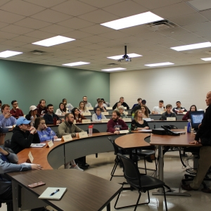 Joe Don Long in front of Global Supply Chain classroom